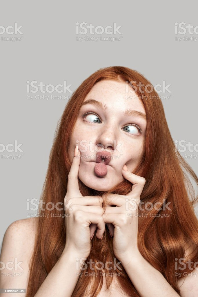 Crazy girl! Close up photo of happy young redhead woman making crazy...