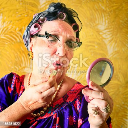 A crazy granny in curlers and cat's eye glasses putting on her makeup. More granny images.
