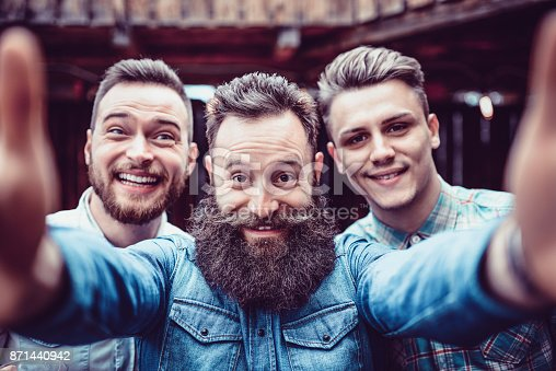 istock Crazy Guys at Pub Drinking Beer and Taking Selfie 871440942