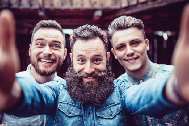 crazy guys at pub drinking beer and taking selfie - beard stock pictures, royalty-free photos & images