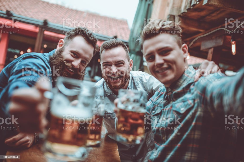 Crazy Guys at Pub Drinking Beer and Taking Selfie stock photo