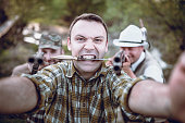Crazy Hunter with Knife in his Mouth Making Selfie with Friend in the Forest