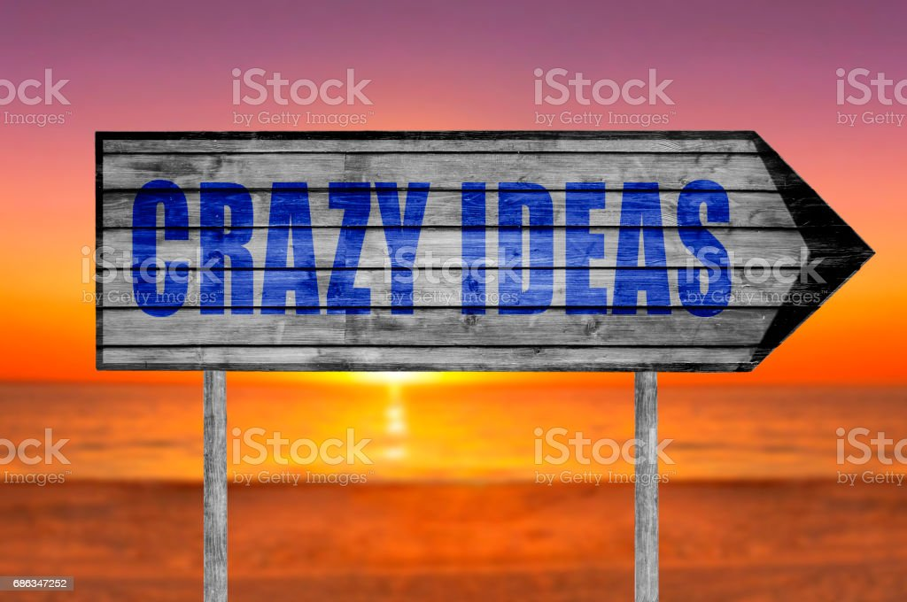 Crazy Ideas wooden sign with a beach stock photo