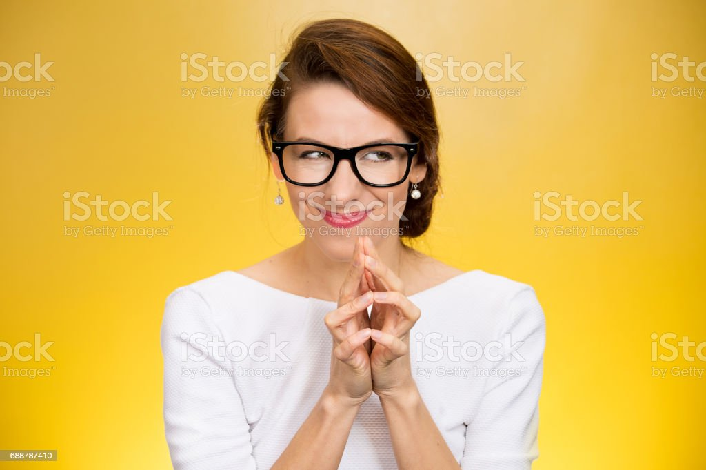 crazy looking sly woman in black glasses crazy looking sly woman in black glasses isolated on yellow background. Adult Stock Photo
