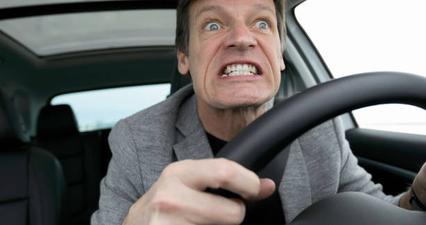 Crazy Mad Car Driver Crazy mad car driver with clinched teeth. Head is partly behind steering wheel. Both hands are on steering wheel. clenching teeth stock pictures, royalty-free photos & images