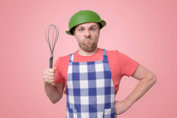 crazy man in an apron with a colander on his head stock photo