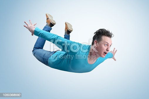 istock Crazy man in shirt and jeans is flying in the sky. Jumper concept 1050368592