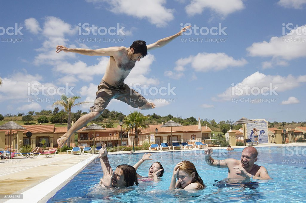crazy man jumping on friends in swimming pool zbiór zdjęć royalty-free