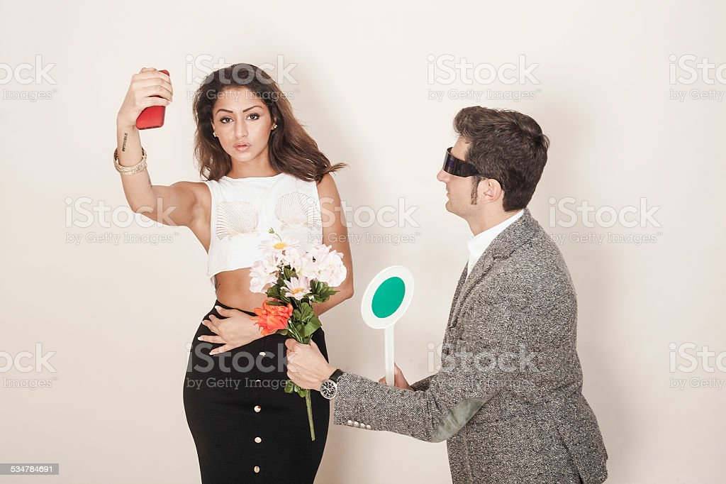Crazy man offering bouquet to a woman who doesn't care stock photo