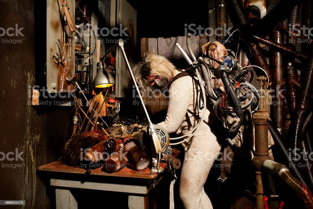 Crazy Masked Mad Scientist in Workshop stock photo