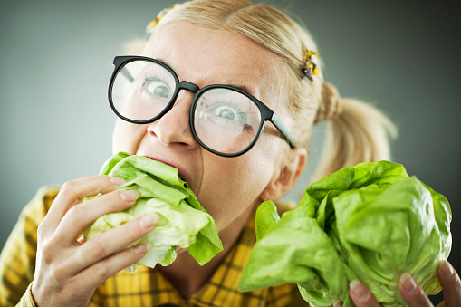 Crazy Nerd Woman With The Cabbage Leaf In Her Mouth Stock Photo - Download Image Now