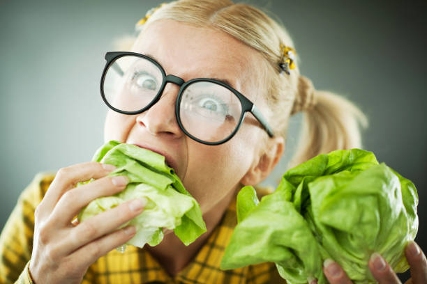 crazy nerd woman with the cabbage leaf in her mouth. - stupidblonde stock pictures, royalty-free photos & images