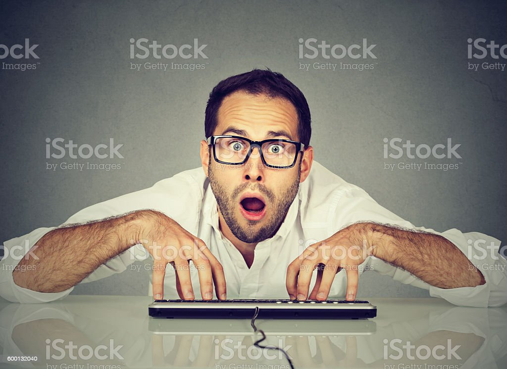 Crazy nerdy looking man in glasses typing on keyboard stock photo