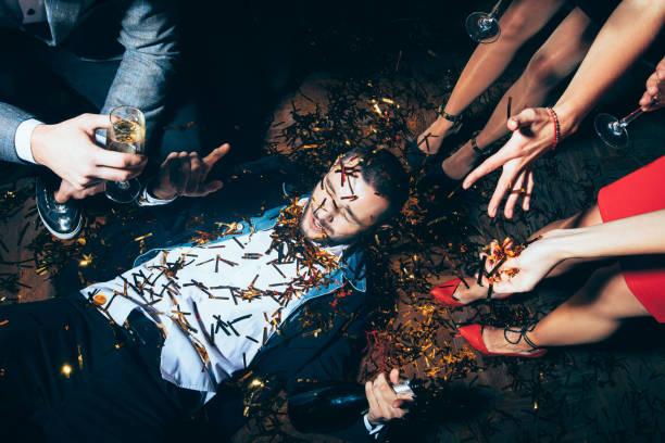 Soirée de folie. Homme ivre allongé sur le sol - Photo