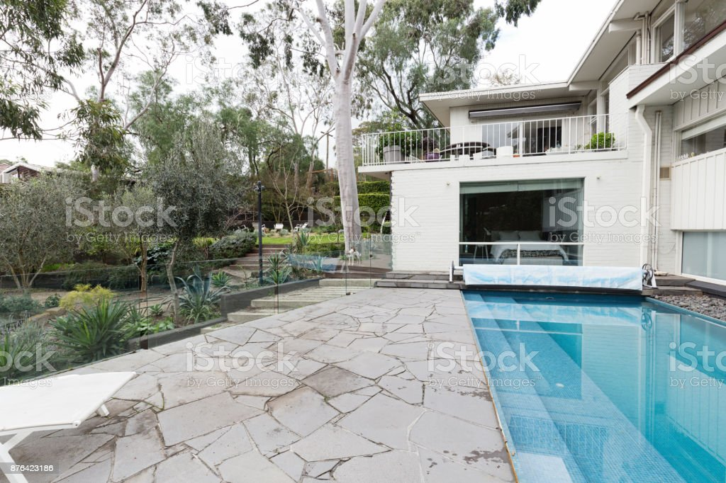 crazy paving beside swimming pool in mid century modern australian home royalty free stock photo