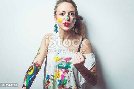 Woman having fun while painting her hands shirt and face with watercolors