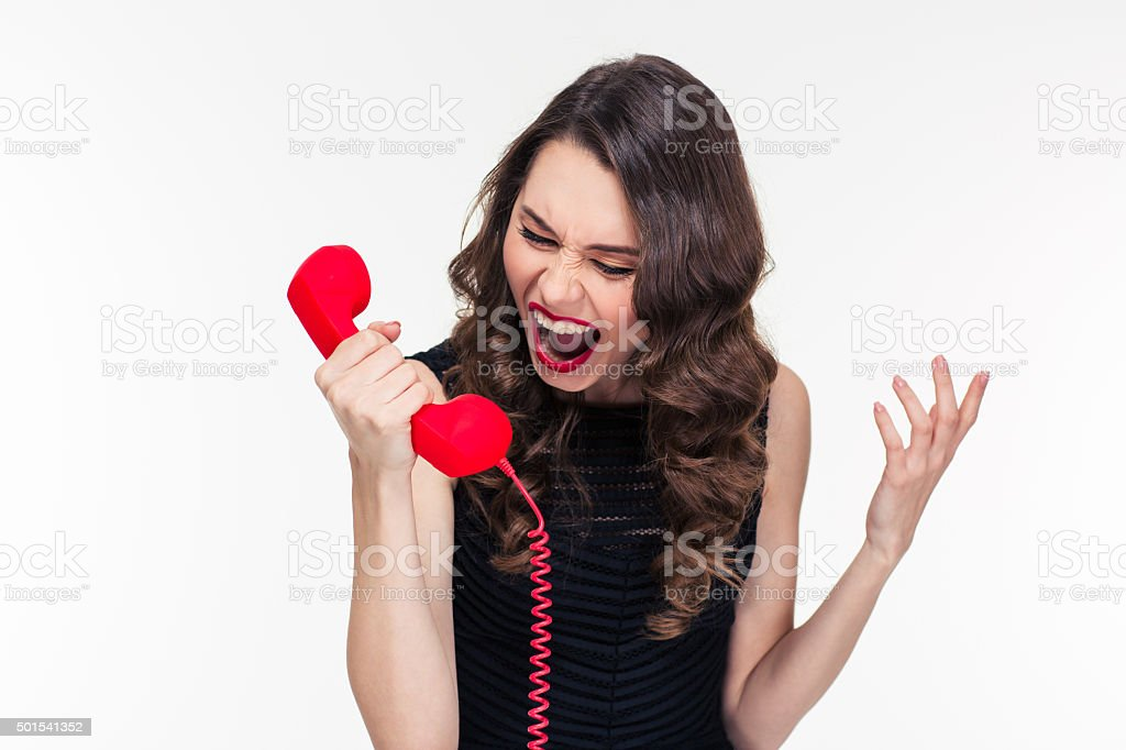 Crazy raged retro styled female shouting in red telephone receiver stock photo