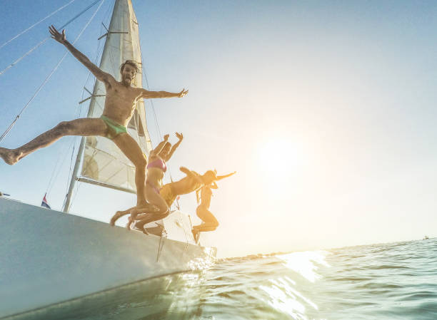 Crazy rich friends jumping off the boat into the ocean - Young happy people having fun diving into the sea at sunset - Travel, tropical, summer, vacation, luxury concept - Soft focus on left man face stock photo
