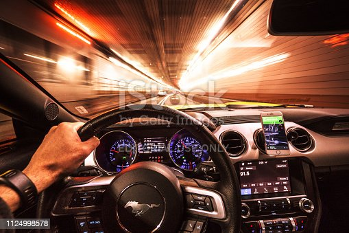 New York City, New York, USA - October 18, 2016: Interior view of a Ford Mustang car dashboard during the night on the traffic inside the new jersey tunnel in new york city.. The Mustang is an iconic american couple made by Ford in USA. The car is running fast in the street during the night.