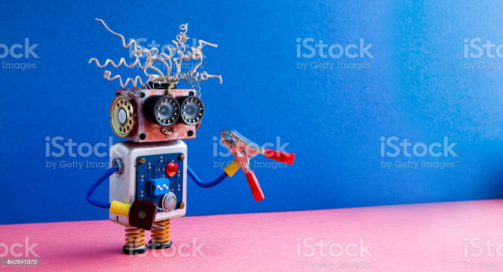 Crazy robot handyman red pliers hand. Funny toy cyborg electric wires hairstyle, big eye glasses, electronic circuit body, red heart. Blue pink background. copy space stock photo