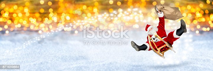 istock crazy santa claus flying on his sleigh snow golden background 871659884