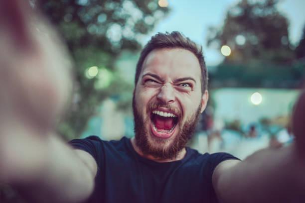 loco gritando selfie toma macho y haciendo muecas al aire libre - poner caras fotografías e imágenes de stock