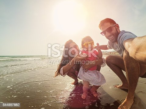 Crazy selfie family with sunglasses on the beach