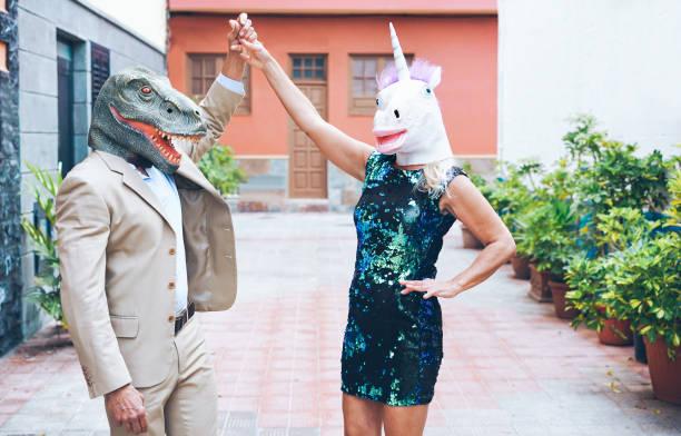 verrückte älteres paar tanzen um stadt straße tragen t-rex und huhn maske - alte trendige leute spaß zusammen-absurde und lustige trend konzept - fokus auf flächen - damen rock kostüme stock-fotos und bilder