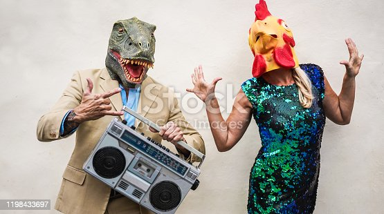 Crazy senior couple dancing at carnival party wearing t-rex and chicken mask - Old trendy people having fun listening music with boombox stereo - Absurd and funny trend concept - Focus on faces