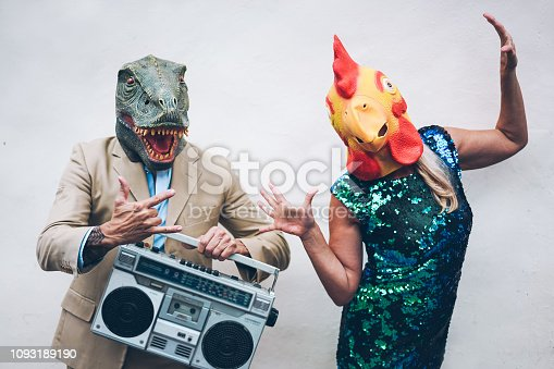 Crazy senior couple dancing for new year's eve party wearing t-rex and chicken mask - Old trendy people having fun listening music with boombox stereo - Absurd and funny trend concept - Focus on faces