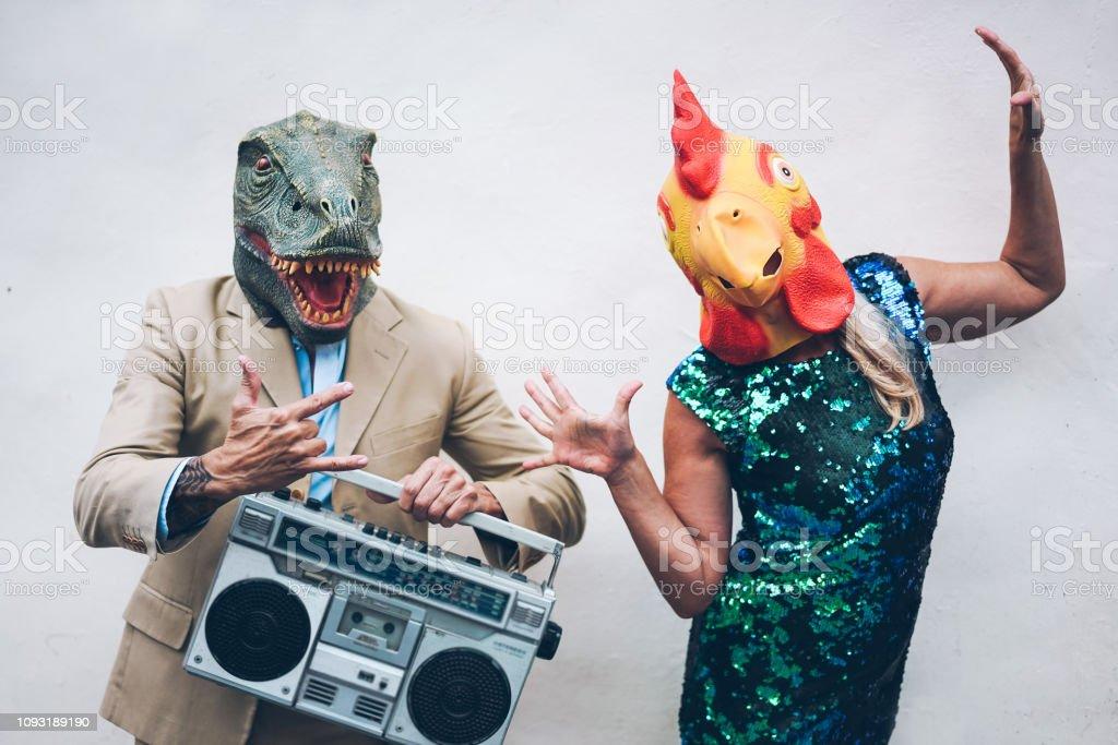 Verrückte älteres paar tanzen für Silvester party tragen t-Rex und Huhn Maske - alt trendige Leute, die Spaß Musik mit Ghettoblaster Stereo - absurde und lustige Trend Konzept - Fokus auf Gesichter – Foto