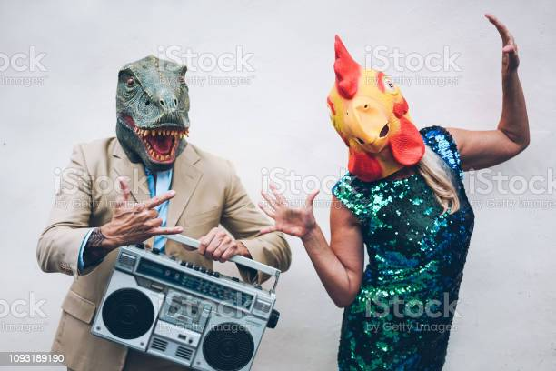 Photo of Crazy senior couple dancing for new year's eve party wearing t-rex and chicken mask - Old trendy people having fun listening music with boombox stereo - Absurd and funny trend concept - Focus on faces