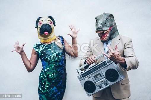 istock Crazy senior couple dancing for party wearing t-rex and chicken mask - Old trendy people having fun listening music with boombox stereo - Absurd and funny trend concept - Focus on dino face 1129136686