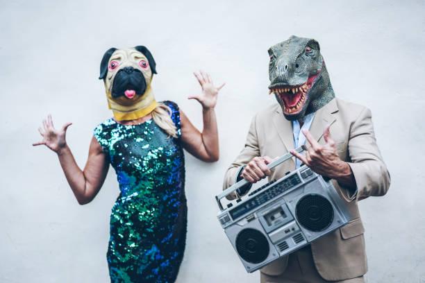 verrückte älteres paar tanzen für party tragen t-rex und huhn maske - alte trendige leute, die spaß musik mit boombox stereo - absurde und lustige trend konzept - konzentrieren sich auf dino-gesicht - damen rock kostüme stock-fotos und bilder