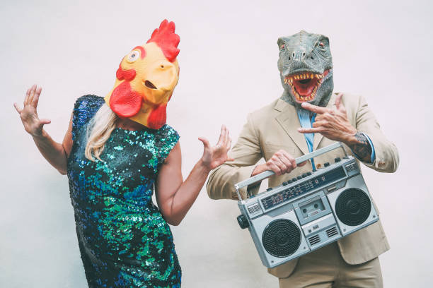 crazy senior couple wearing chicken and t-rex mask while dancing outdoor - mature trendy people having fun celebrating and listening music with boombox - absurd concept of masquerade funny holidays - eccentrico foto e immagini stock