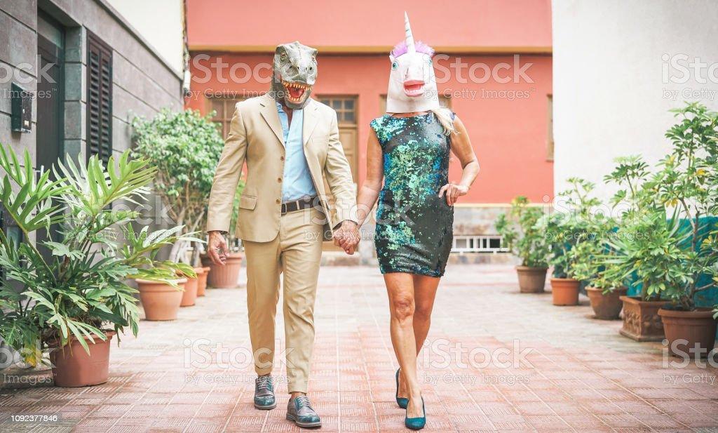 Crazy senior par bär dinosaurie och unicorn mask - mogen trendiga människor ha kul maskerad på carnival parade - absurt, excentrisk, surrealistiskt, fest och roliga maskerad koncept - Royaltyfri Aktiva pensionärer Bildbanksbilder