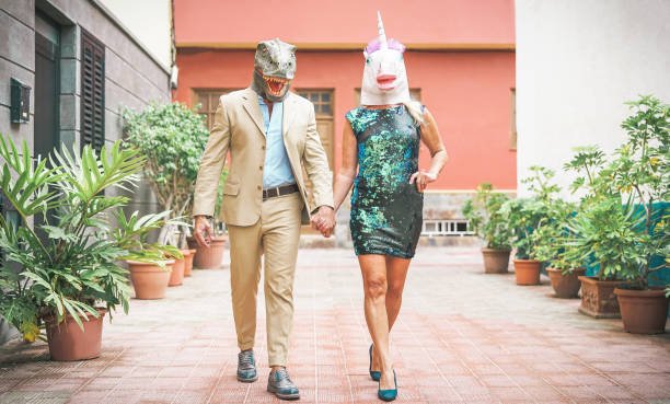 Crazy senior couple wearing dinosaur and unicorn mask - Mature trendy people having fun masked at carnival parade - Absurd, eccentric, surreal, fest and funny masquerade concept Crazy senior couple wearing dinosaur and unicorn mask - Mature trendy people having fun masked at carnival parade - Absurd, eccentric, surreal, fest and funny masquerade concept costume stock pictures, royalty-free photos & images