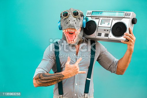 istock Crazy senior man dancing rock music wearing t-rex mask - Tattoo trendy guy having fun listening music with boombox stereo - Absurd and funny trend concept - Focus on face 1135963253