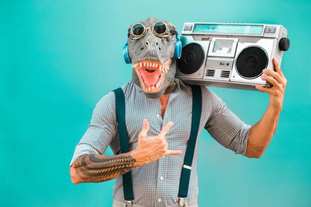 verrückte seniorenmannes tanzen rockmusik mit t-rex-maske-tattoo trendiger kerl, der spaß am hören von musik mit boombox-stereo hat-absurd und lustiges trendkonzept-focus on face - faschingskostüme herren stock-fotos und bilder