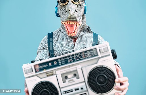 istock Crazy senior man wearing t-rex mask and listening to music holding vintage boombox stereo outdoor - Fashion masquerade male having fun dancing and celebrating outside - Absurd and funny people concept 1144429584