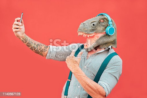 istock Crazy senior man wearing t-rex mask and taking selfie with mobile smartphone - Hipster older male having fun listening music and dancing outdoor -  Absurd, funny and surreal concepts 1140567123