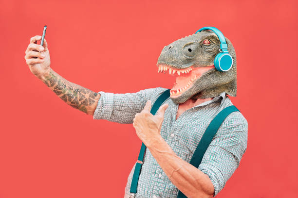 Crazy senior man wearing t-rex mask and taking selfie with mobile smartphone - Hipster older male having fun listening music and dancing outdoor -  Absurd, funny and surreal concepts Crazy senior man wearing t-rex mask and taking selfie with mobile smartphone - Hipster older male having fun listening music and dancing outdoor -  Absurd, funny and surreal concepts amusing stock pictures, royalty-free photos & images