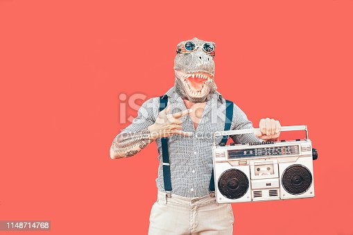 istock Crazy senior man wearing t-rex mask while listening to music holding vintage boombox stereo outdoor - Fashion masquerade male having fun dancing and celebrating - Absurd and funny people concept 1148714768