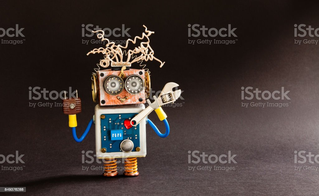 Crazy serviceman robot ready with adjustable spanner. Creative design cyborg toy, electric wires hairstyle, big eyeglasses, electronic circuit body, red heart. black background copy space stock photo