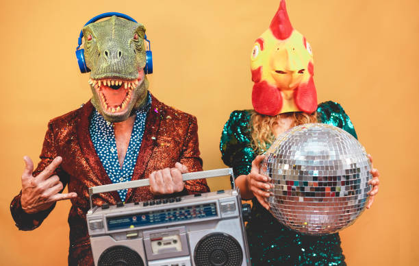 Crazy stylish people listening music with vintage boombox stereo - Fashion couple wearing t-rex and chicken mask at party fest event -  Absurd, holidays and funny trend concept - Focus on man face stock photo