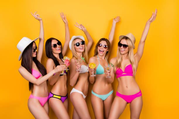 Swimpool folle partie de poule! Danser et aller fou! Cinq dames mignonnes sont posant sur fond jaune clair en maillots de bain et lunettes de soleil, casquettes, avec levé les mains, vin et champagne, martini - Photo