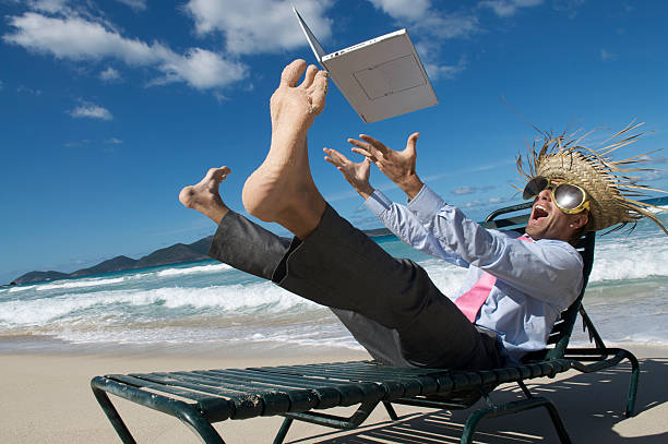 Crazy Tourist Businessman Throws His Laptop Up Tropical Beach stock photo