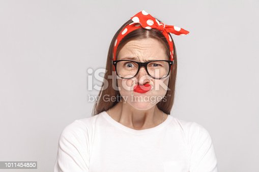 istock crazy wondered funny portrait of beautiful emotional young woman in white t-shirt with freckles, black glasses, red lips and head band. 1011454850