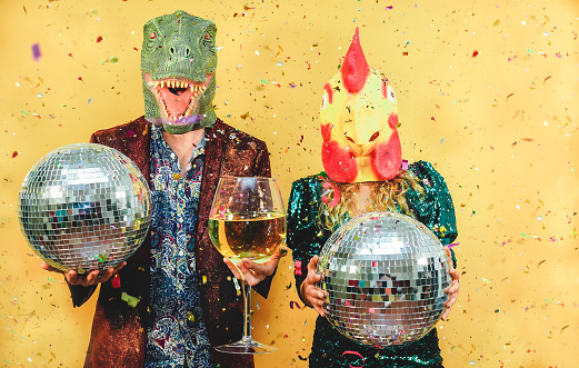 istock Crazy young couple having fun for new year's eve party wearing t-rex and chicken mask - Fashion people celbrating at fest event - Absurd, holidays and funny trend concept - Focus on faces 1194857317