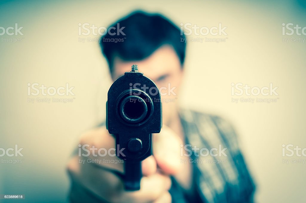 Crazy young man aiming gun at you stock photo